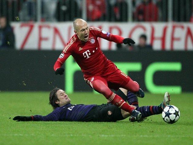 Tomáš Rosický z Arsenalu (vlevo) dostal za skluz na Arjena Robbena z Bayernu Mnichov žlutou kartu.