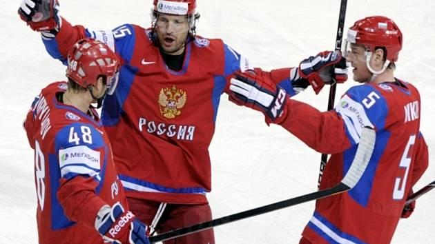 Hokejisté Ruska (zleva) Jevgenij Birjukov, Alexander Svitov a Ilja Nikulin se radují z gólu proti Lotyšsku.