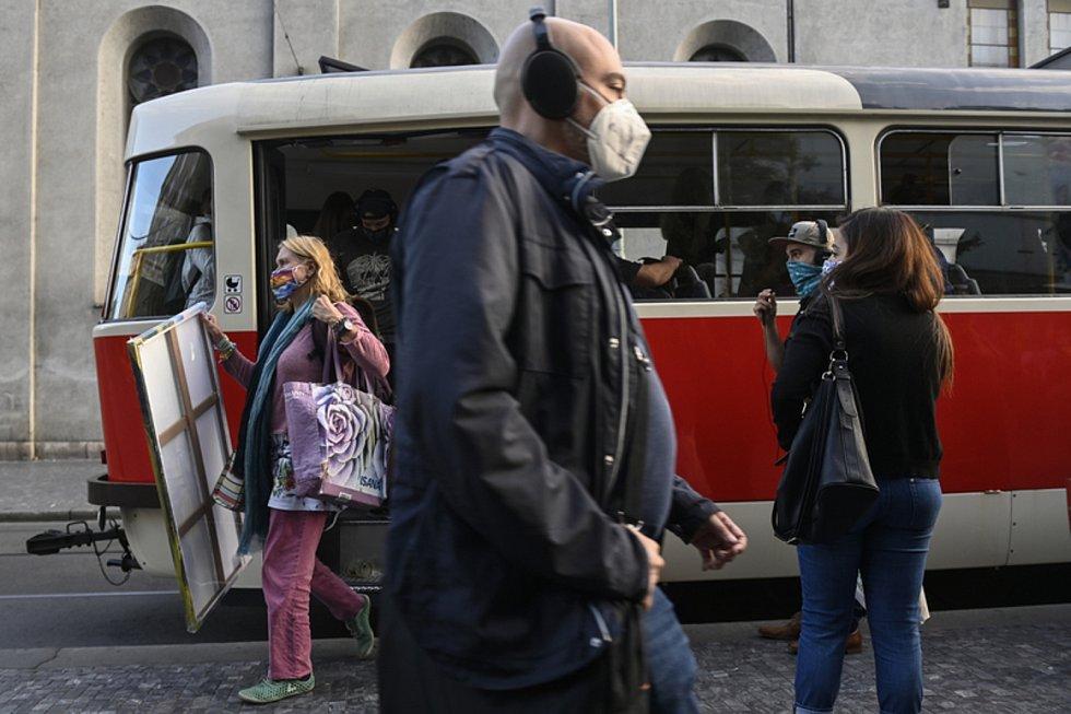 Lidé s rouškami na obličejích na tramvajové zastávce v Praze na Andělu