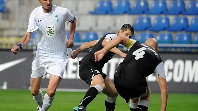 Adrian Rolko (vlevo) z Boleslavi v souboji s Kevinem Hoflandem a Alberto Serranim z AEK Larnaka.
