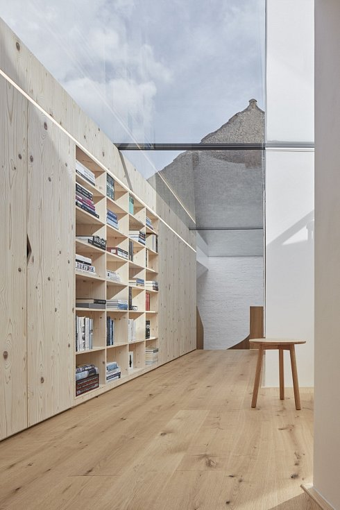 netradičním a překvapivým prvkem je chodba, která propojuje nové domy, tedy obývák s ložnicí – působí spíš jako vložená průhledná krychle.