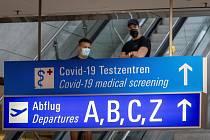 Lidé s rouškami na letišti ve Frankfurtu.