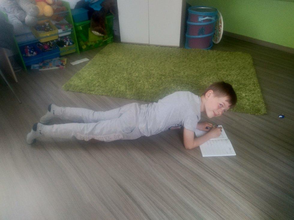 Syn píše úkol při planku-inspiroval se Olgou Roučkovou.Zkusil to a teď cvičí stále.