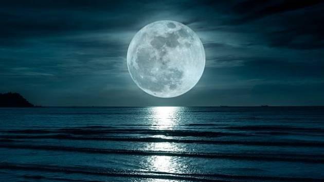 Měsíc v úplňku nad oceánem.