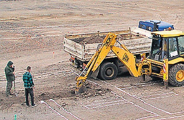 Stavební stroje čistí pozemek po armádě.