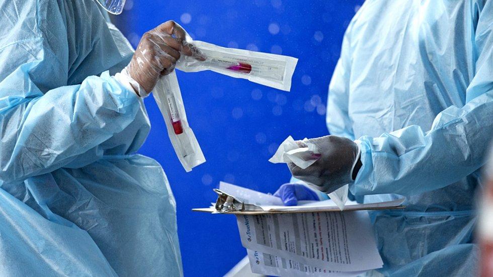 Testování na koronavirus v USA - Zdravotníci se sadami pro odběr vzorků na koronavirus v testovacím centru v Miami v USA.
