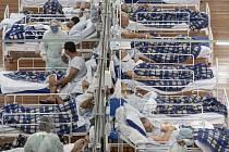 Pacienti s koronavirem leží na lůžkách v polní nemocnici v tělocvičně v Santo Andre, na okraji Sao Paula.