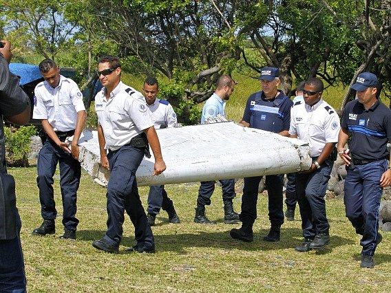 Policisté odnášejí úlomek letadla nalezený na ostrově Reunion.