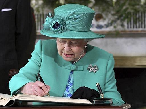 Královna Alžběta II. se na své první návštěvě Irska podepisuje do knihy hostů v prezidentském paláci v Dublinu