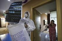 Lékař v ochranném oděvu si prohlíží rentgenový snímek během kontroly pacientů držených v karanténě kvůli koronaviru.