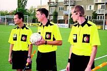 Fotbaloví rozhodčí se sluchátky.