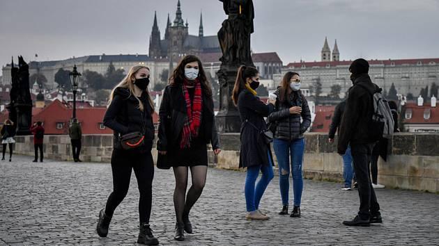 Lidé v rouškách 22. října 2020 na pražském Karlově mostě. Kvůli šíření nemoci covid-19 vstoupilo v platnost vládní nařízení omezení pohybu a kontaktu s jinými lidmi. Výjimkou jsou cesty do práce, na nákupy, k lékaři nebo za rodinou