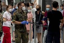 Voják pomáhá organizovat zájemce o testování na letišti ve Frankfurtu