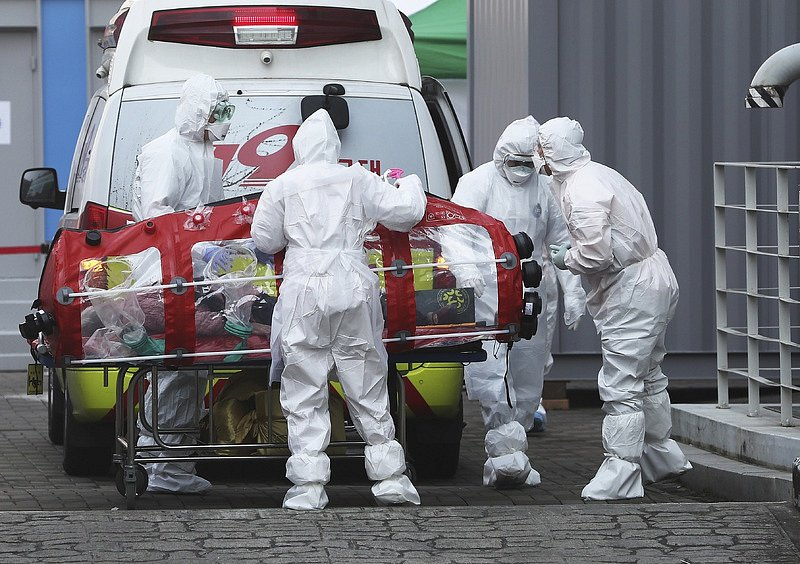 Zdravotníci v ochranném oděvu převážejí pacienta infikovaného koronavirem do nemocnice v Soulu.