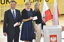 Prezidentský kandidát Andrzej Duda s manželkou a dcerou u volební urny.