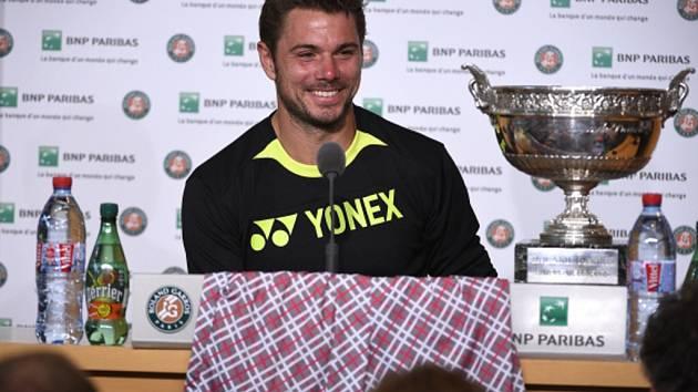 Stan Wawrinka s trofejí pro vítěze Roland Garros a s vítěznými šortkami.