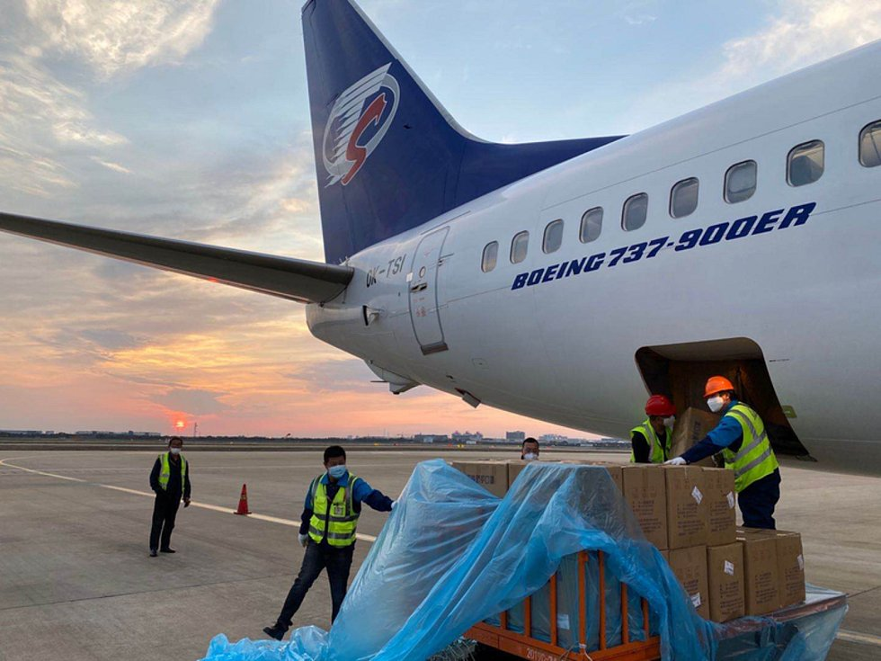 Personál nakládal 23. března odpoledne na letišti v Šanghaji další ochranné prostředky pro zvládání epidemie koronaviru.