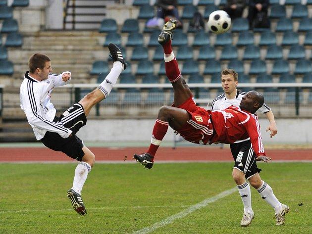 Dani Chigou (uprostřed) z Dukly Praha se snaží prosadit proti hráčům Hradce Králové. Utkání nakonec skončilo bez branek.