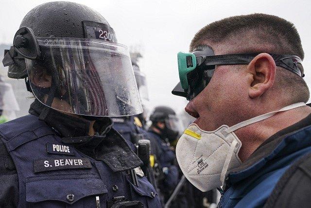 Policista tváří v tvář demonstrantovi před Kapitolem.