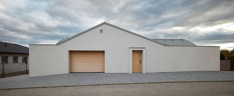 Kratší z jeho dvou ramen zabírá garáž, dílna, technické zázemí a vstup se šatnou, umývárnou a toaletou.