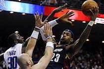 Hvězda basketbalistů Clevelandu LeBron James (v tmavém) se snaží prosadit přes bránícího dvojblok Bass, Gortat.