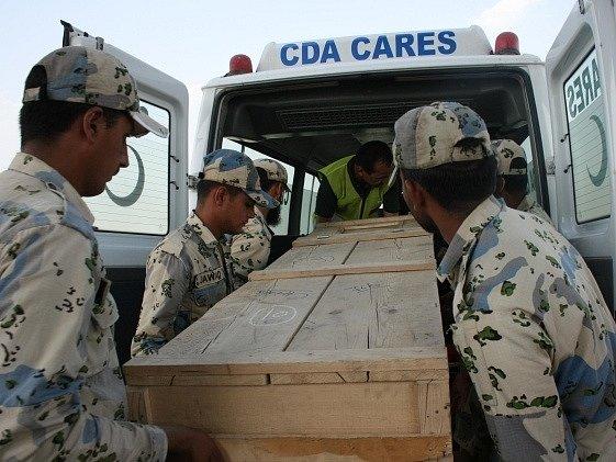Vojáci nakládají rakev jedné z obětí.