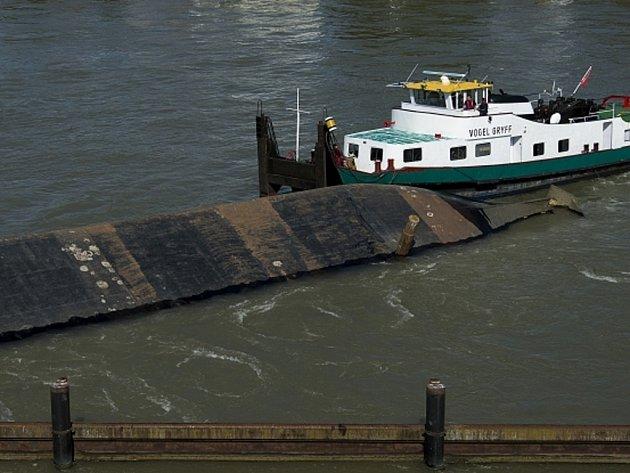 Převržené plavidlo je upevněno vlečnou lodí, unikla z něj nafta.
