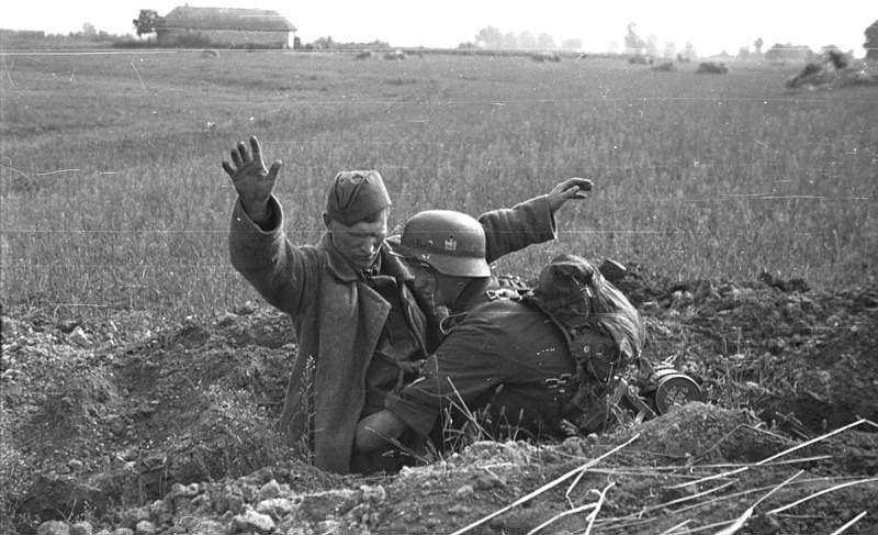 Německý voják odzbrojuje sovětského vojáka ve střeleckém zákopu