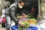Prodavač zeleniny na trhu v čínském městě Wu-chan