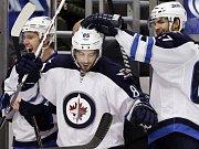 Hokejisté Winnipegu (zleva) Jacob Trouba, Mathieu Perreault a Michael Frolík se radují z gólu.