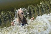 Dívka se osvěžuje u vody v horkém letním počasí. Ilustrační foto.