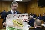 Bývalý hejtman Středočeského kraje David Rath ukazuje obrázek s kritikou pomalé práce justice v soudní síni krajského soudu v Praze.