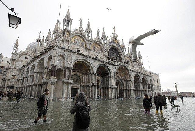 Kvůli silným dešťům jsou ulice Benátek pod vodou. Turisté se brodí ve vodě po kolena.