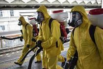 Pracovníci v ochranných oděvech se chystají k dezinfikování nástupišť vlakového nádraží v Moskvě, 19. května 2020.