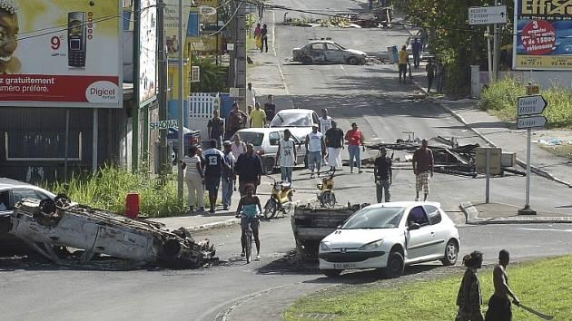 Mladíci s mačetami poblíž vraků a trosek, které tvoří barikádu na ulici Abymes, poblíž guadeloupského Pointe-e-Pitre.
