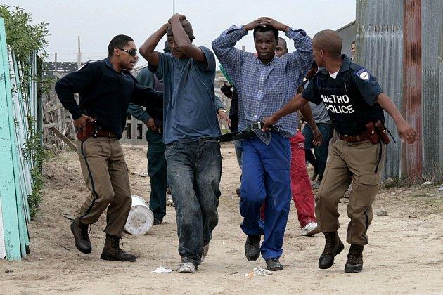 Policie odvádí mladé Jihoafričany, kteří v pátek zaútočili na imigrantský slum Khayelitsha nedaleko Kapského města.