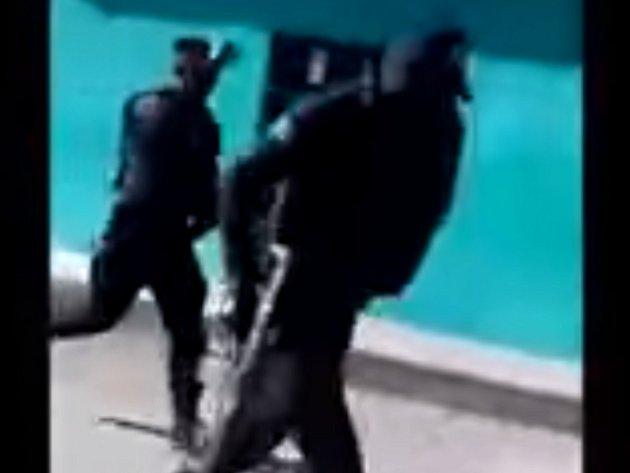 Dvojice ozbrojených policistů prchá od zločinu. Video pořídila jedna z místních žen na mobilní telefon.