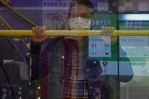 Muž v roušce v autobusu v Hongkongu na snímku ze 17. března 2020