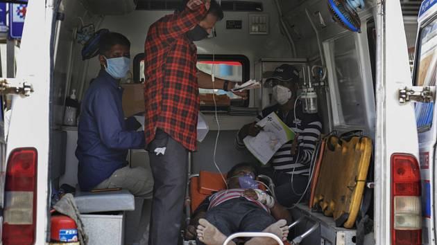 Pacient s covidem-19 čeká v sanitce za pomoci příbuzných na přijetí v nemocnici v indickém městě Ahmadábád