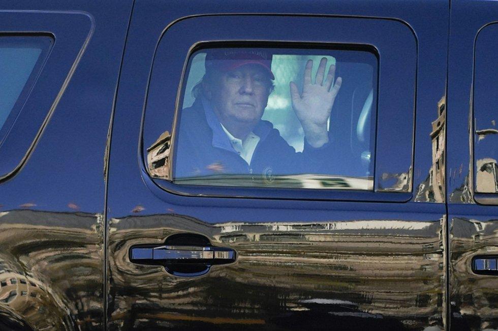 Americký prezident Donald Trump zdraví z limuzíny své příznivce.