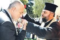 Mluví neformálně, obléká se neformálně a jde z něj respekt. Nový bulharský premiér Bojko Borisov (vlevo) včera představil svou menšinovou středopravou vládu. Na snímku mu žehná kněz.