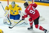 Brankář Švédska Jacob Markström kryje střelu Samuela Walsera ze Švýcarska.