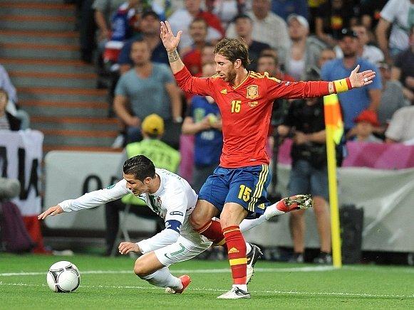 Ronaldo z Portugalska se snaží vymodlit si penaltu na Sergio Ramosovi ze Španělska.