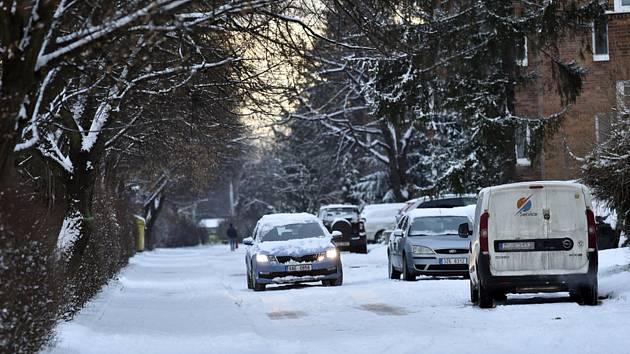 Automobil 13. ledna 2021 projíždí zasněženou ulicí na sídlišti Obeciny ve Zlíně
