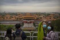 Lidé v rouškách v pekingu 25. dubna 2020, v pozadí turistická atrakce Zakázané město