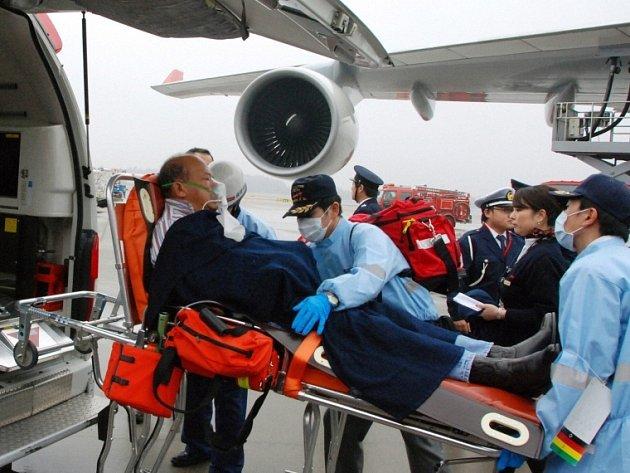 Zraněný cestující z letadla postiženého turbulencí je převážen do ambulance na japonském letišti Narita.