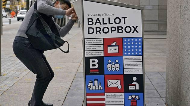 Muž hází hlasovací lístek do volební schránky před veřejnou knihovnou v americkém Bostonu