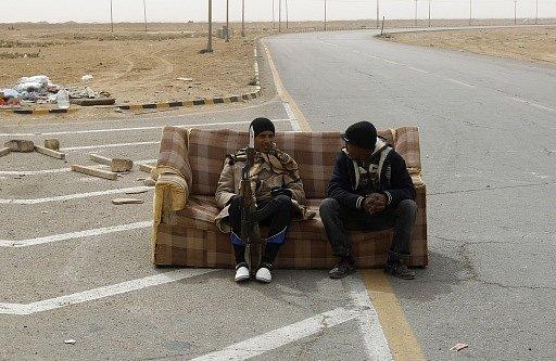 Povstalci  odpočívají  na gauči na kontrolním stanovišti v Ajdabiyahu, Libye, 15. března 2011