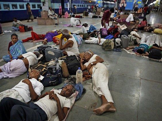 Lidé znavení vedrem odpočívají na nádraží v Allahabadu.