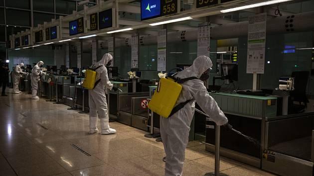 Španělští vojáci dezinfikují prostory terminálu letiště v Barceloně 19. března 2020
